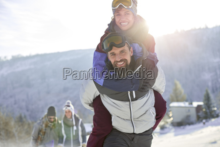 portrait playful couple piggybacking in sunny