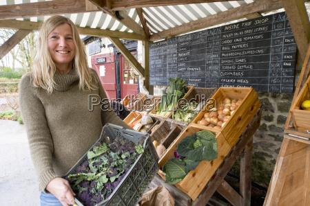 woman running stall selling organic fruit
