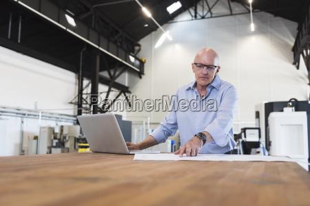 man with laptop looking at plan
