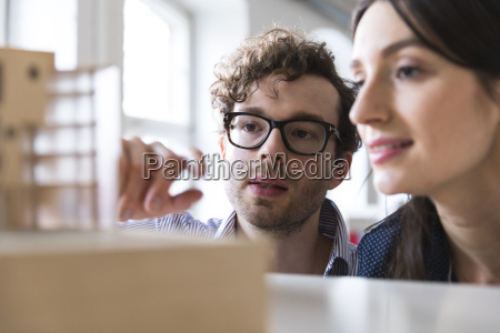 man and woman discussing architectural model