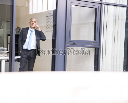 mature businessman in office using smartphone