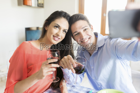 couple holding red wine glasses posing