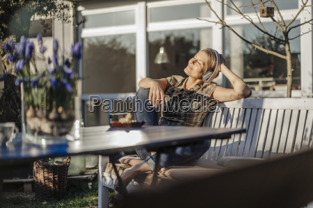 woman wearing headphones relaxing on garden