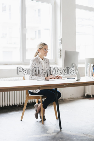 businesswoman sitting at desk working with