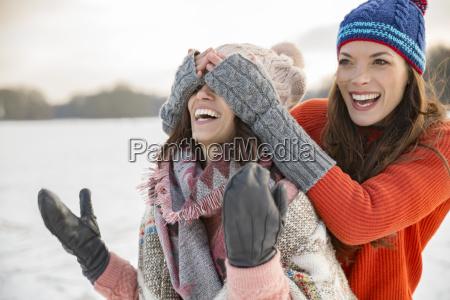 playful friends on frozen lake
