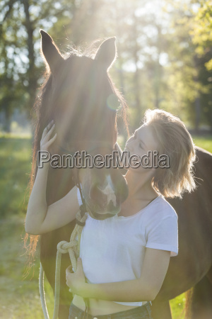 young woman with horse at backlight