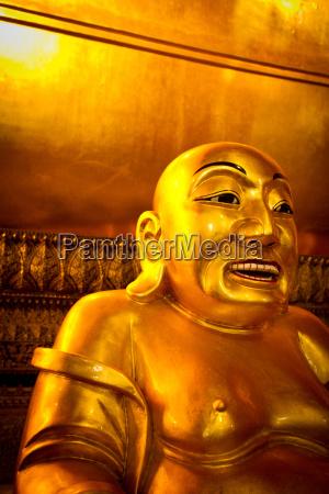 a smiling buddha inside wat pho