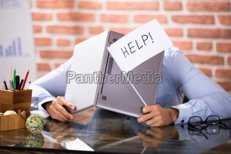 businessman covering his head with laptop