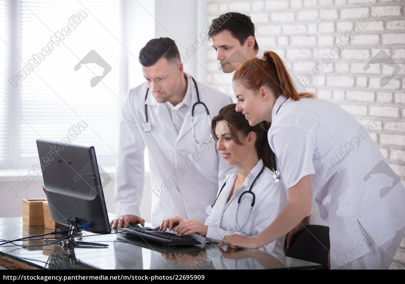 group, of, doctors, looking, at, computer - 22695909