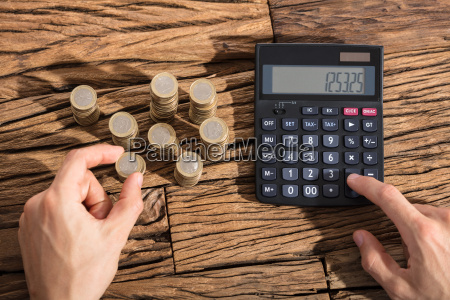 person, calculating, coins, on, calculator - 22695625