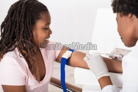 doctor injecting patient with syringe to