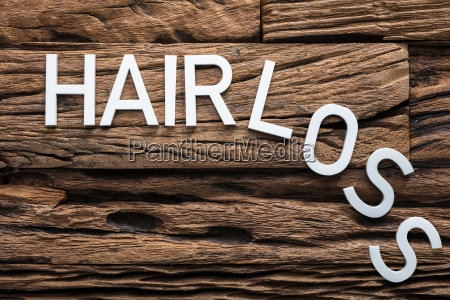 white hair loss text on wood