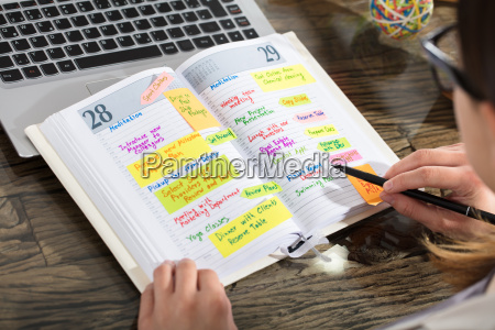 businessperson, writing, schedule, in, diary - 22696659