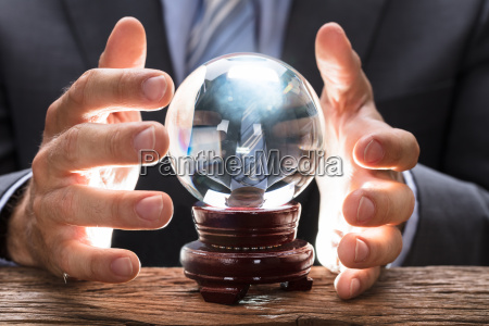 midsection, of, businessman, covering, crystal, ball - 22696973
