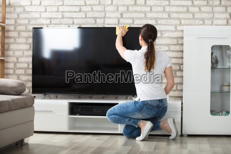 woman, wiping, the, television, screen, at - 22696749
