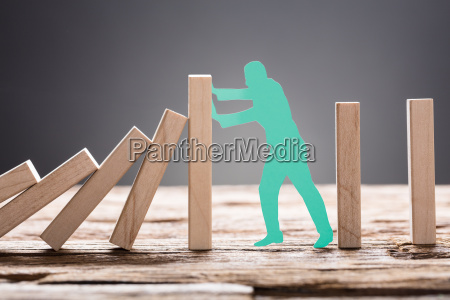 green paper man stopping wooden domino