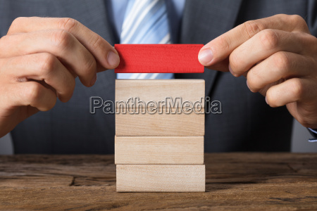 businessman placing red block on wooden