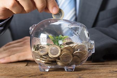 businessman, putting, coin, into, transparent, piggybank - 22697071