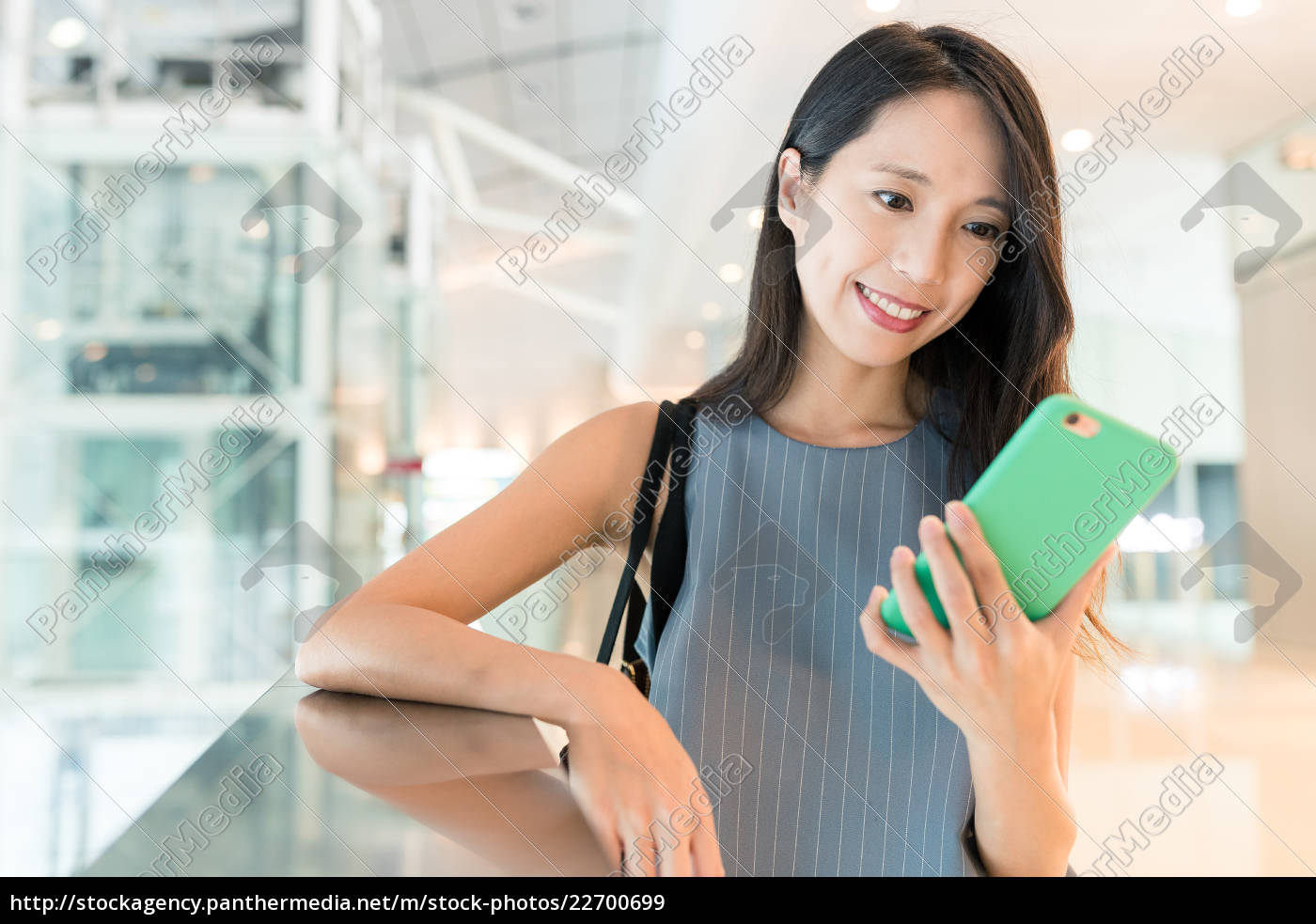 woman, holding, cellphone, in, shopping, mall - 22700699