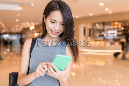 woman, looking, cellphone, in, shopping, mall - 22700695