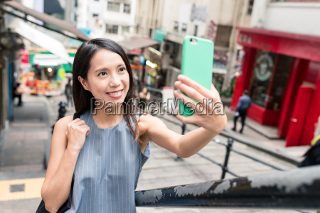 woman, taking, photo, with, cellphone, in - 22700709