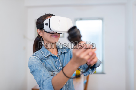 young, woman, play, with, vr, device - 22700617