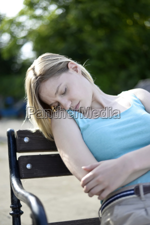 young woman is sleeping on bench