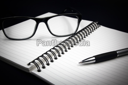 notebook glasses and pen on black
