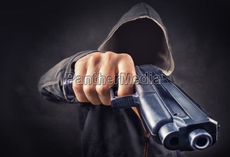 faceless man with a pistol in