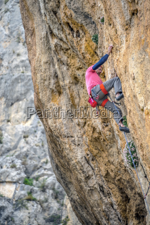 man climbing difficult route on rock