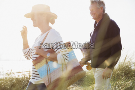 mature couple walking in sunny beach