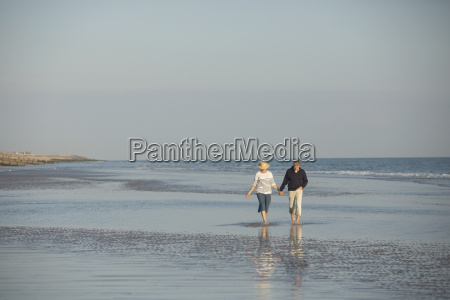 mature couple holding hands walking in