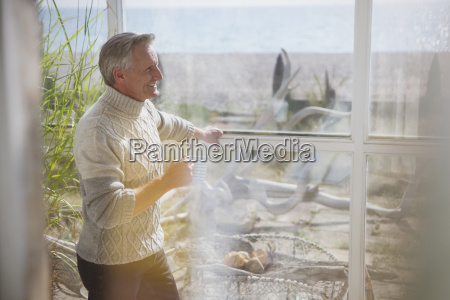 mature man in turtleneck sweater drinking