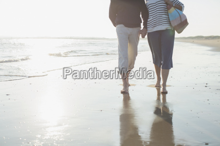 affectionate barefoot mature couple walking holding