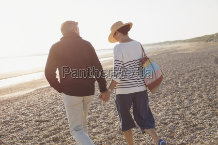 affectionate mature couple holding hands walking