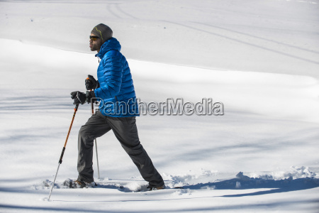 man walking in snow on sunny