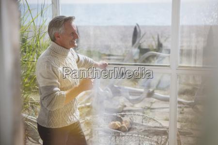 mature, man, in, turtleneck, sweater, drinking - 22716465