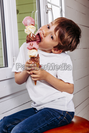 young boy eating a tall ice