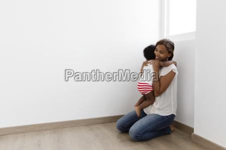 woman kneeling on a wooden floor