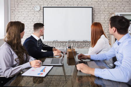 business people looking at white board