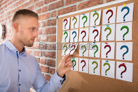 businessman looking at question marks on