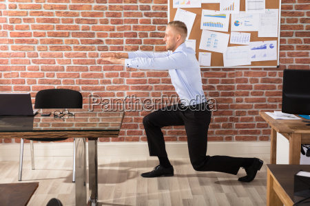 businessman, doing, exercise, in, office - 22721265
