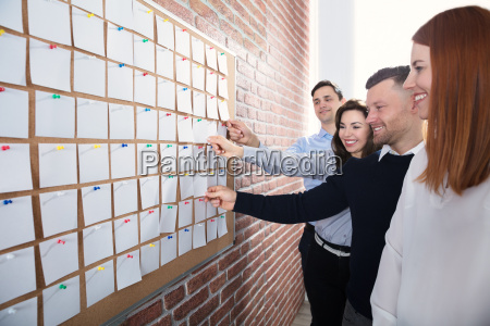 hands, holding, paper, notes, on, corkboard - 22721249