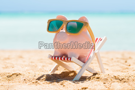 piggy bank with wooden sunglasses on