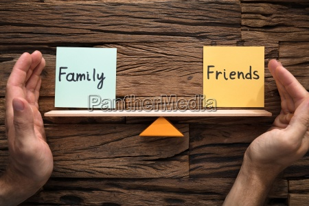 hands covering balance between family and