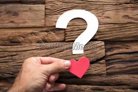 hand holding question mark with heart