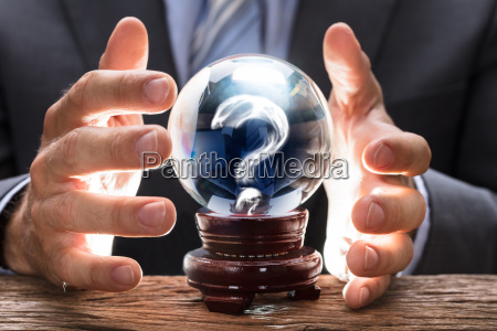businessman covering crystal ball with question