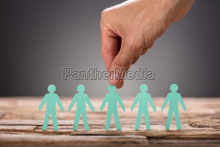 hand picking green paper man representing