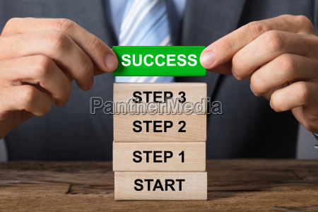 businessman building success concept with wooden