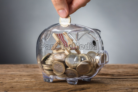 hand putting coin in transparent piggy